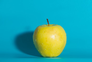 on a blue background yellow Apple, close up.
