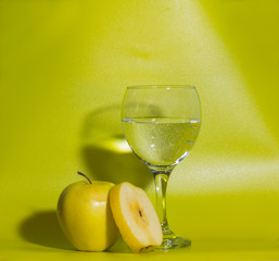 on a green background yellow apples with a glass of water.