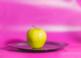 on a pink background on the plate yellow Apple.