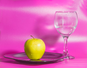 on a pink background on the plate yellow Apple with a glass of water.