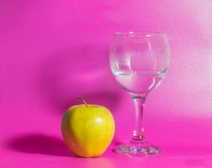 on a pink background yellow Apple with a glass of water.