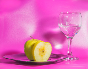 on the plate is yellow Apple with a glass of water on a pink background.