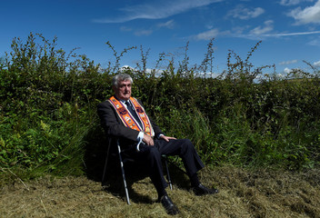 An observer waits for the Orange Order march to pass, on its way to Rossnowlagh in County Donegal