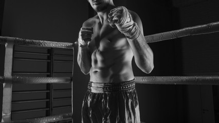 Kickboxer stands in the corner of the ring in an attacking rack
