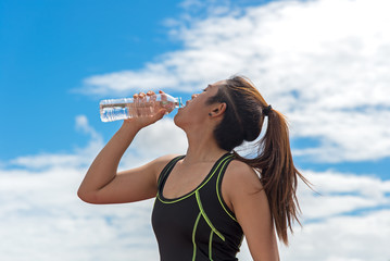 Sport woman holding a water bottle after exercise,back ground blue sky. Healthy Concept