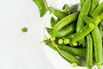 Green peas in a white plate.