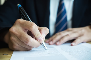 Business man signing business contract agreement, businessman handwriting signature on Formal Paper contract document at office desk