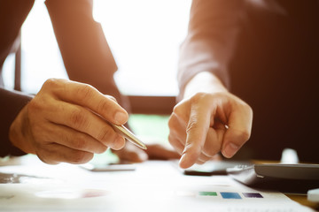 Business man pointing to financial graph in the conference.Business meeting time working with new startup project.Notebook and laptop on wood table.presentation concept, Accounting analyze plans.