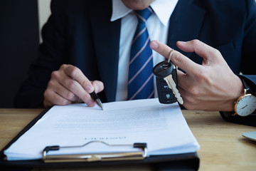 Successful businessman offering a car key with contract.Rental agreement for a car with contract.Car Insurance