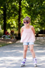 Little girl with sunglasses on in-line skates