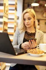 Young woman with laptop and mobile
