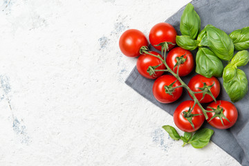 Fresh cherry tomatoes with basil leaves, top view with copy space