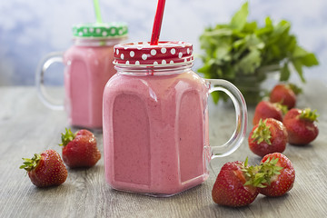 Strawberry smoothies in a glass bottle, mint leaves and whole strawberry berries on a gray wooden background.