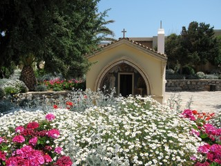 Charming floral decor, island of Crete, Greece/Simple daisies and other meadow and field flowers are parts of landscape designs. Spring. Away Christian chapel. From travels in Mediterranean