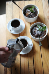 Dessert healthy breakfast of oat pudding in a white keraimic mold. Moka coffee in white cups