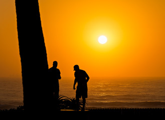 Surfers silhouette against the ocean at sunrise in Durban South Africa