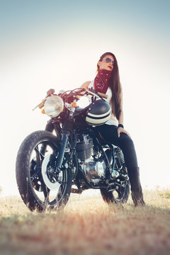 Fashion female biker girl. Young Woman sitting on vintage custom motorbike.