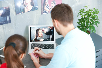Two young photographers discussing picture on laptop display