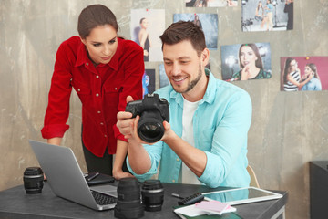 Two young photographers discussing picture on camera display