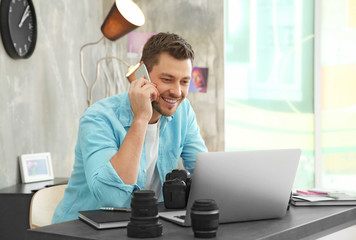 Photographer working with laptop in office and talking on phone