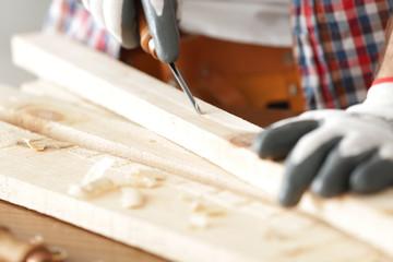 Carpenter carving timber in workshop, closeup