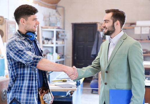 Handshake between carpenter and customer in workshop