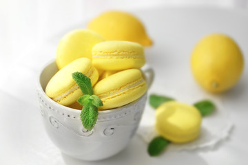 Fototapete - Cup with tasty lemon macarons on table, closeup