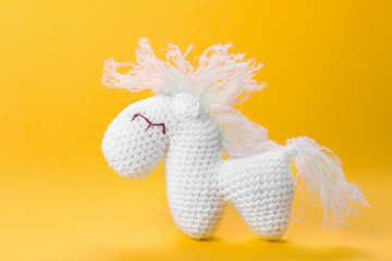 Adorable knitted horse baby toy on color background, closeup