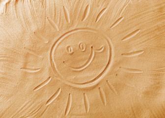 Sun drawn on sea sand, closeup view