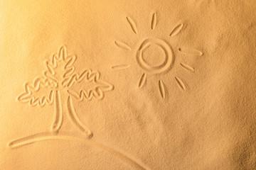 Palm and sun drawn on sea sand, closeup view