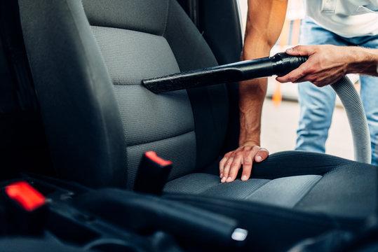Man cleans car interior with vacuum cleaner