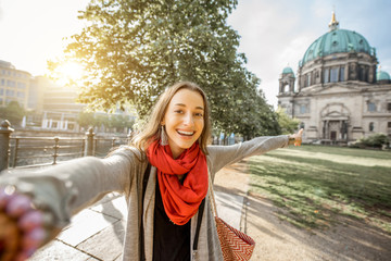 Young woman tourist making selfie photo in front of the famous cathedral in Berlin city
