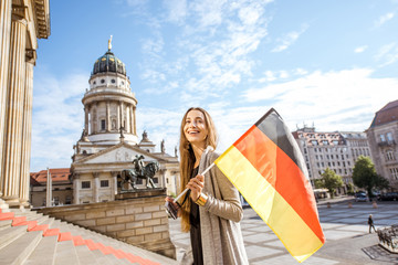 Young woman tourist walking with german flag on the stairs near the Concert house in Berlin
