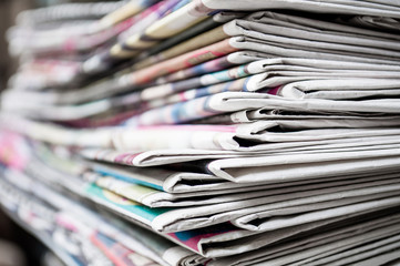 Newspapers folded and stacked on the table background. Colorful newspaper. Image shallow depth of field.