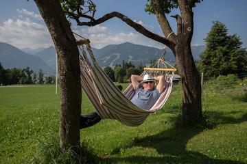Älterer Herr in einer Hängematte im Freien mit Bergen im Hintergrund