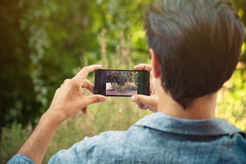 young man take photo with smartphone outdoor