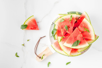 Fresh ripe juicy organic raw watermelon, cut into pieces. On a white marble plate, marble table, with mint leaves. Food background. Copy space