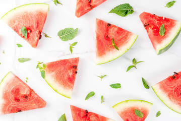 Fresh ripe juicy organic raw watermelon, cut into pieces. On a white marble table, with mint leaves. Pattern. Food background. Top view copy space