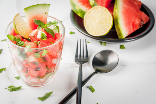 Mexican food. Summer berries and fruits. Vegetable salsa salad with watermelon, tomatoes, onions, greens, lime. In portioned glass on white marble table, with the ingredients. Copy space