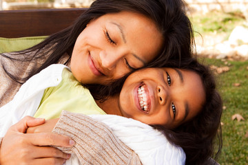 Biracial mother and daughter laughing and smiling outside.