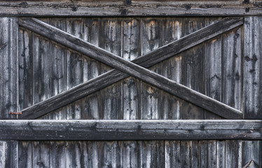 Vintage rural gate of barn with cross from laths.