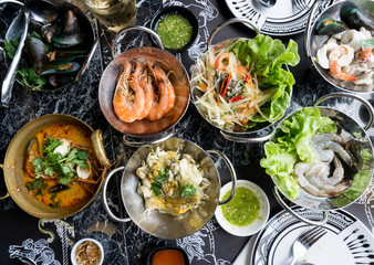 Thai seafood on table Include Tom Yum Goong, Papaya salad, Oyster Omelette, Raw shrimp. .