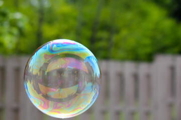 house reflected in a bubble on the left  floating past a out of focus fence