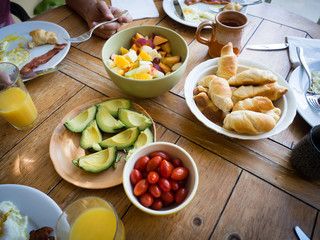 Healthy American breakfast with fruit salad, tomatoes, avocado, eggs, bacon, bread, orange juice on farm style wood table