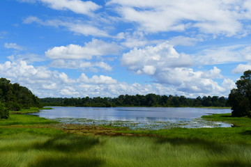 Photo picture a blue sky and a lake, meadow grass and clouds float white