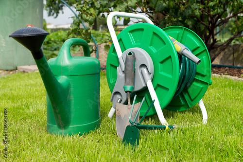 Gartenzubehör  Gartenzubehör / Gartenschlauch und Gartenwerkzeug in einem Garten ...