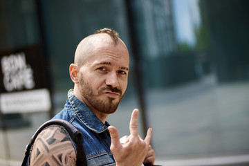 Smiling young male fan of heavy metal music with beard and mohawk hairstyle standing on street and showing horns gesture at camera. Outdoor shot of stylish tattooed man giving rock and roll sign