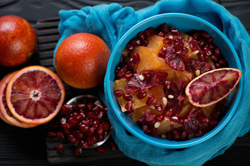 Fruit salad with oranges and pomegranate seeds, high angle view on a black wooden surface, horizontal shot