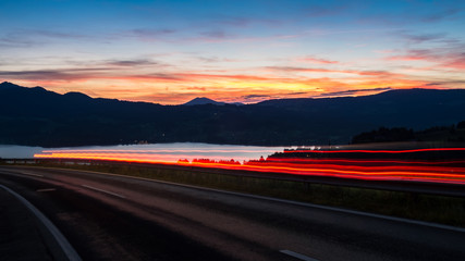 Austrian countryside road car is passing during the sunset only light rays are visible lacke is on the background