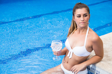 Attractive girl standing with wineglass and laughing in swimming pool.